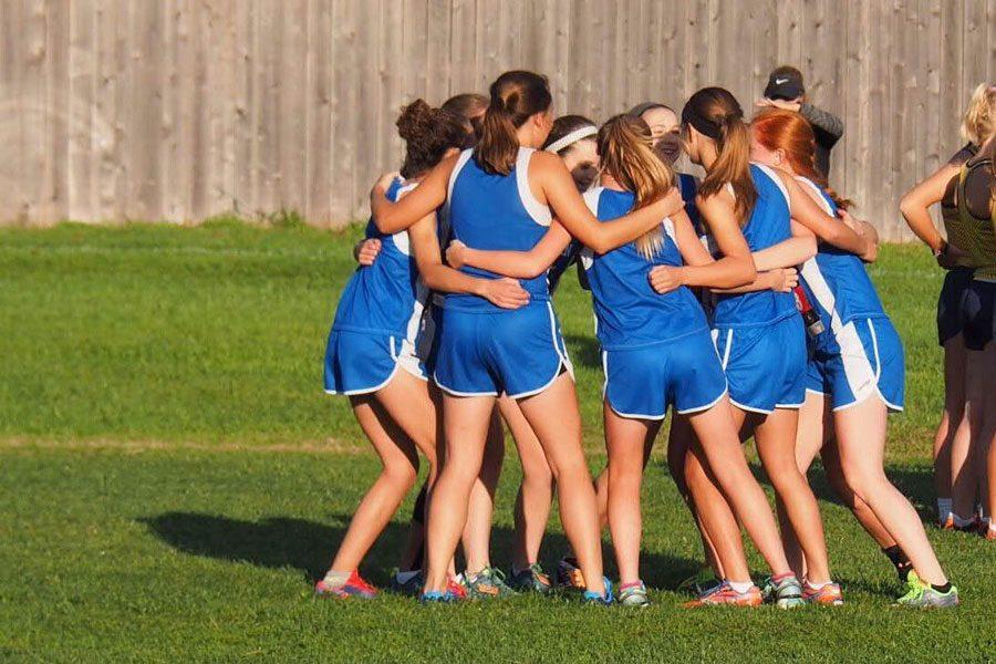 The girls cross country team huddles up before their first meet at Johnson County Community College on Sept. 3.