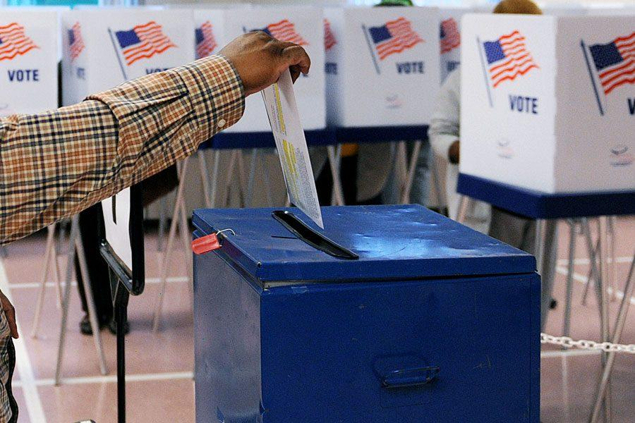 A voter drops his ballot into the ballot box during early voting in Ohio.