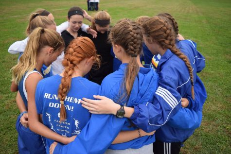 The girls cross country team huddles before the League meet at Felker Park on Oct. 15.