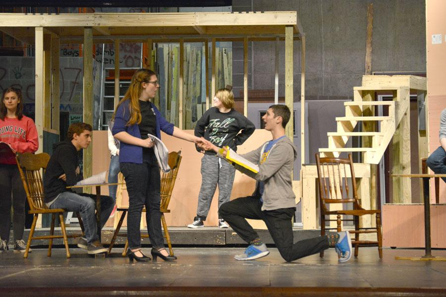 Senior John Katz, who plays Bobby Child, kneels and proposes to Polly Baker, who is played by senior Shannon Nelson during rehearsal on Jan. 12.